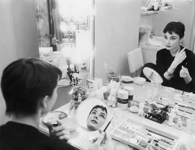"Audrey Hepburn at Make Up Table in Two Mirrors. Audrey Hepburn photographed for Mademoiselle in 1954 in her dressing room backstage at Ondine. After years of perfect blondes, Audrey's look was fresh and new ""…Beauty is again human instead of heavenly and we have Miss Hepburn to thank for it."" The source for this image was a vintage 35mm black and white negative."