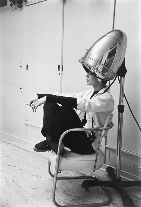 Photographed for LIFE in 1953, Audrey Hepburn, under the hair dryer, smokes a cigarette. While working on the film Sabrina, Audrey was shampooed every night and often conducted business with her agents while under the dryer. The source for this image was a vintage 35mm black and white negative.