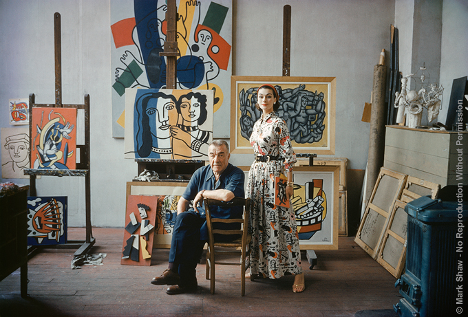 Fernand Leger with Model. Photographed by Mark Shaw for LIFE in 1955, two weeks before his death, Fernand Leger posed for this final portrait in his Paris Studio. Leger's studio is the one he had worked in since 1913. British model Anne Gunning wears an ankle length gown by American Fashion Designer Claire McCardell. The Fabric's pattern is in the style of Leger's work best seen in the painting of two women (left) and in the half hidden still life. The source for this image was a vintage 35mm color transparency.