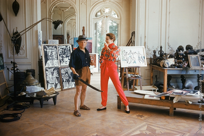 Picasso with Bettina and Sword. Photographed for LIFE in 1955 in his new Cannes Villa, La Californie, Picasso celebrates his Fashion debut by clowning around with a fedora and a sword. Top French Model, Bettina Graziani wears an outfit by American Fashion Designer Claire McCardell. The shirt's pattern is in the style of a Picasso still life. All the Picasso paintings pictured had been completed within the past few months. The source for this image was a vintage 35mm color transparency.