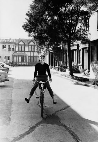 Photographed For The December 1953 Issue Of LIFE, Audrey Hepburn Rides A Bike From The Makeup Department To The Set Where Filming Began At 9 O'clock. The Source For This Image Was A Vintage 35mm Black And White Negative.