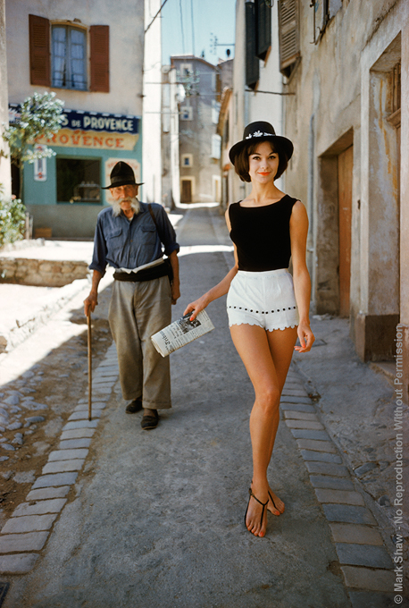 "St. Tropez Model in Shorts with Admirer. Photographed by Mark Shaw for the article ""The St. Tropez Way for the U.S.A."" from the Jan 13, 1961 issue of Life, model ""Irene"" is wearing shorts by Angelo. The source for this image was a vintage 35mm color transparency."