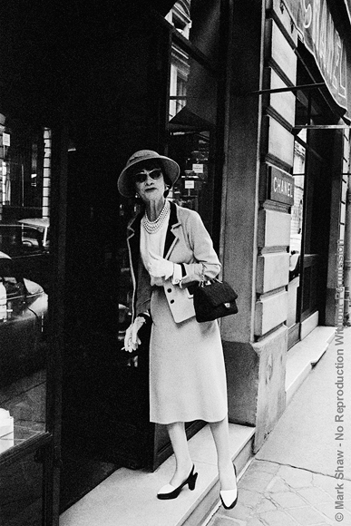 "Coco Enters her Shop on the Rue Fauborg St. Honore, 1957. Photographed in 1957, Coco Chanel is seen entering her boutique in Paris. According to LIFE, Coco is ""…credited with either inventing or popularizing the short skirt, the flat chest, the sling pump, turtlenecks…"" She is shown here in her ""ever present"" hat. "" The only reason I wear my hat all the time is so I can tell people I don't want to see that I am on my way out"". Mark Shaw's informal, grainy, black and white images of Coco Chanel were created using an unobtrusive 35mm camera and film processing methods that enabled him to eliminate all other photographic equipment. Although Shaw's techniques increased the grain and contrast of the photographs, the lack of intimidating, distracting flash and lights allowed him to capture an unusually relaxed Chanel. The source for this image was a vintage 35mm black and white negative."