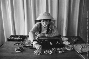 "Coco Chanel Creates Jewelry In Her Workroom. She Works With Plasticine Surrounded By Boxes Overflowing With ""jewels."" Mark Shaw's Informal, Grainy, Black And White Images Of Coco Chanel Were Created Using An Unobtrusive 35mm Camera And Film Processing Methods That Enabled Him To Eliminate All Other Photographic Equipment. Although Shaw's Techniques Increased The Grain And Contrast Of The Photographs, The Lack Of Intimidating, Distracting Flash And Lights Allowed Him To Capture An Unusually Relaxed Chanel. The Source For This Image Was A Vintage 35mm Black And White Negative."