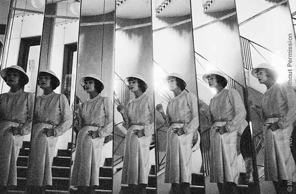 Chanel's famous mirrored staircase was a favorite photographic location. Mark Shaw's informal, grainy, black and white images of Coco Chanel were created using an unobtrusive 35mm camera and film processing methods that enabled him to eliminate all other photographic equipment. Although Shaw's techniques increased the grain and contrast of the photographs, the lack of intimidating, distracting flash and lights allowed him to capture an unusually relaxed Chanel. The source for this image was a vintage 35mm black and white negative.