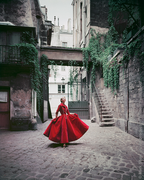 "Courtyard Chanel Red Velvet Dinner Dress, Cour de Rohan, 1955. A velvet dinner dress by Chanel, is photographed in the vine hung Paris courtyard, Cour de Rohan, in 1955. The source for this image was a 4"" x 5"" vintage color transparency."
