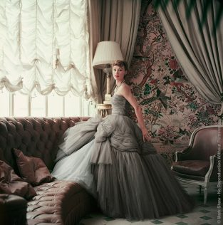 "Sophie Malgat Wears Dior In Dior's Passy Home, 1953. Sophie Malgat In Gray Chiffon Dior In Dior's Paris Home. Outtake From A Shoot For Life Nov. 9, 1953 Issue. Mark Shaw's Camera Captured This Dior Clad Model In The Sunroom Of Dior's Home In Passy. The House Was Originally Built In The Early 1900's For An Actress Of The Comedie Francaise. The Source For This Image Was A Vintage 2.25"" X 2.25"" Color Transparency."