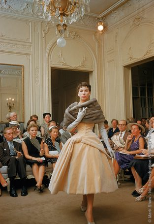 Salon Dior Cream Velvet Fur Stole. Photographed In 1954 For LIFE By Mark Shaw In The Dior Salon, Buyers And Other Important Guests View A Model Wearing A Cream Velvet Tea Length Gown With Fur Stole. The Source For This Image Was A Vintage 35mm Color Transparency.