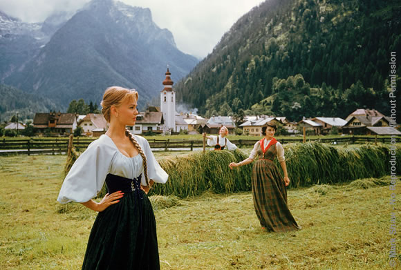 Three Models in McCardell, Austria, 1956. Photographed for LIFE August 1956, models wearing Claire McCardell creations pose in an alpine valley near the village of Lofer, Austria. The backdrop of church steeples shows the influence of Byzantine architecture. The source for this image was a vintage 35mm color transparency.