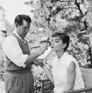 "Audrey Hepburn, Wally Westmore On The Set Of Sabrina, R2_2. Audrey Hepburn And Makeup Artist Wally Westmore On The Set Of Paramount's Sabrina Fair. The Source Of This Image Was A Vintage 2.25"" X 2.25"" Black And White Negative."